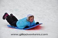 child sledding in the snow